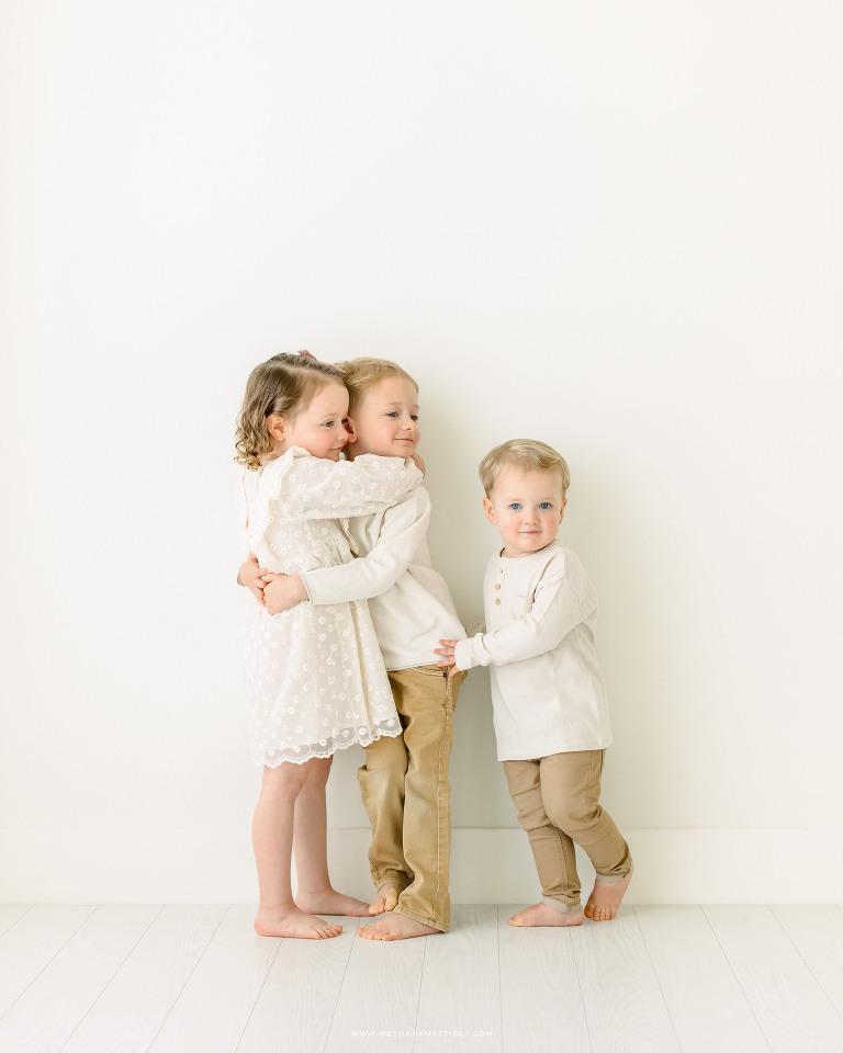 Three Siblings Hugging wearing neutral clothing